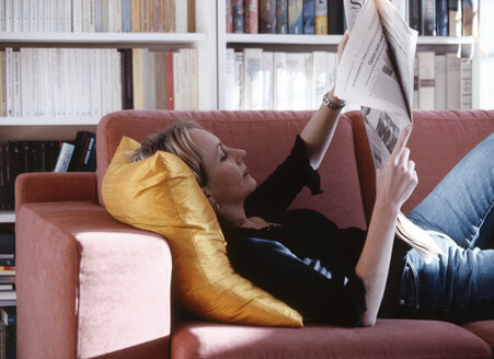 Young woman reading newspaper on sofa - PE00157