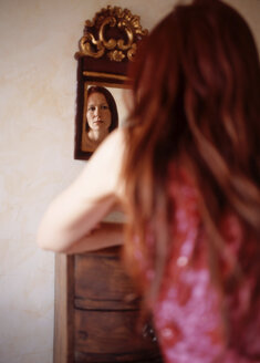 Red haired woman looking in mirror, rear view - PE00124