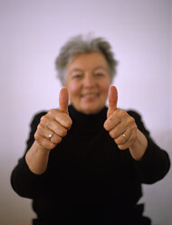 Senior woman showing thumb up sign, smiling, portrait - DK00065