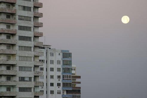 old living blocks in front of a dull gray sky with a full moon, Havana, Cuba - 00041BM-U