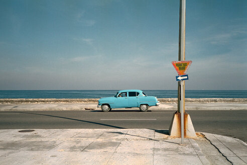 Blue car on road in front of ocean - 00002BM-U