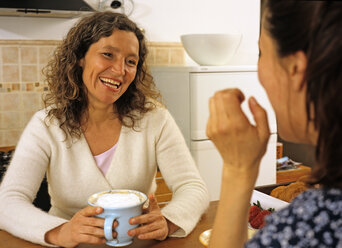 Women sitting with coffee in kitchen - PE00217
