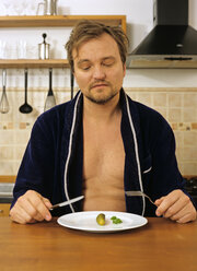 Mature man sitting to eat cucumber with fork and knife - PE00205