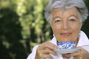 Senior woman holding cup of tea, close-up - PEF00329