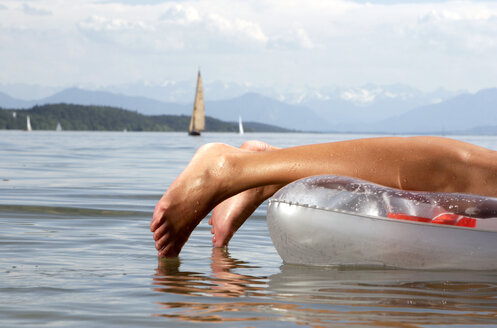 Woman on air mattress lying on front, Lake Starnberg - LDF00057
