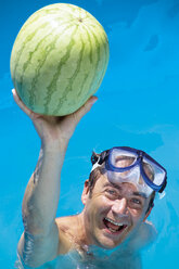 Man in swimming pool playing with  water melone - 02168CS-U
