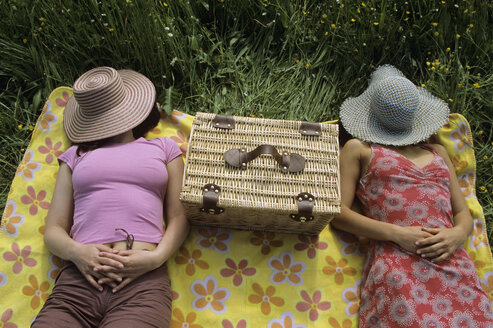 Women relaxing in meadow with hat over face - LDF00069