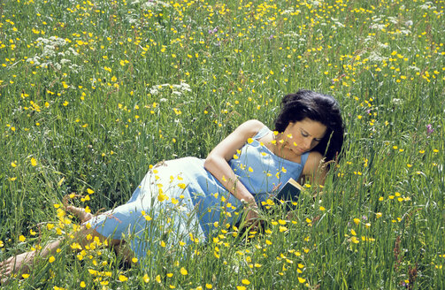 Young woman lying on grass reading book, elevated view - LDF00084