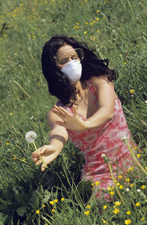 Woman wearing a mask and protective goggles sitting in a meadow, avoiding pollen - LD00110