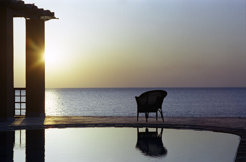 Chair by beach swimming pool at sunset - UKF00061