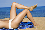 Woman relaxing on beach, side view, low section - LDF00115
