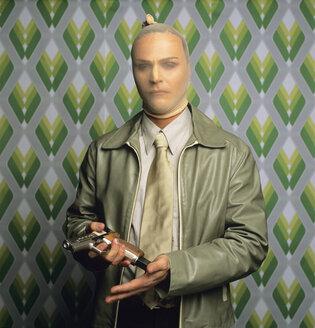 Robber in disguise holding gun, portrait - JLF00046