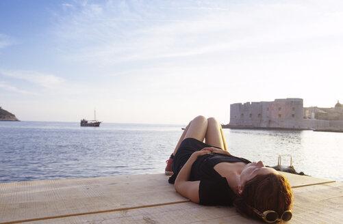 Croatia, Dubrovnik, woman lying on pier - GSF00514