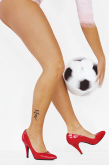 Woman with red high heels holding soccer ball - LRF00007