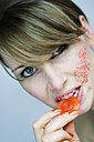 Young woman eating fruit jelly, portrait, close-up - MFF00058
