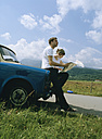 Couple with map, leaning on car - NH00054