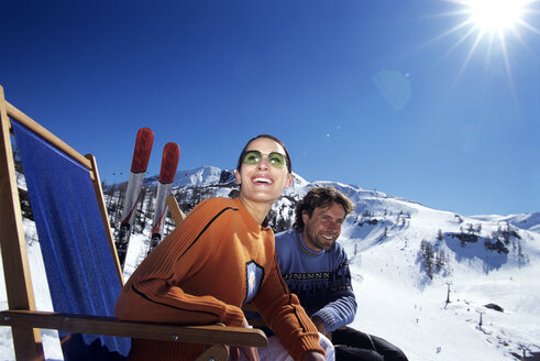 Couple relaxing on deckchair in alps, smiling - HHF00185