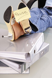 Woman at work with feet up on files - 00038LRH-U