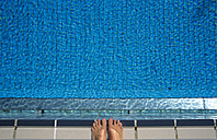Feet at edge of swimming pool, elevated view - GWF00243
