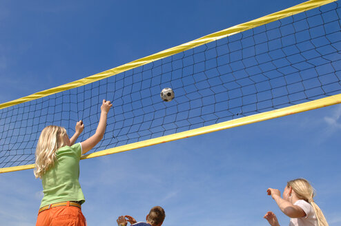 Children (6-9) playing volleyball, low angle view - CRF00875