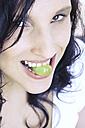 Woman holding grape between teeth - MAEF00005