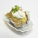 Baked potato with sour cream in foil, close-up - WESTF00404