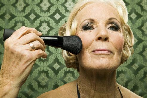Senior woman with make up brush - WEST00353