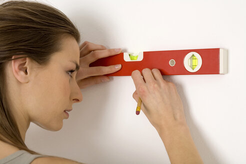 Young woman using spirit level, marking wall with pencil, smiling - WESTF00479
