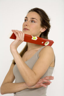 Young woman holding red spirit level, close-up - WESTF00476