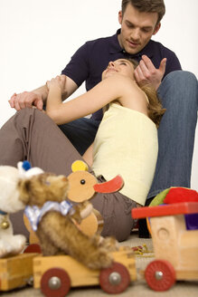 Young couple sitting on floor with toys - WESTF00461