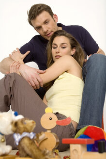Young couple sitting on floor with toys, close-up - WESTF00458