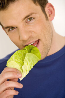 Young man eating lettuce leaf, close-up - WESTF00523