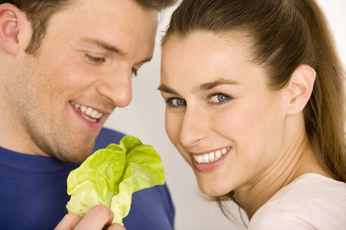 Young couple with lettuce leaf, smiling, close-up - WESTF00520