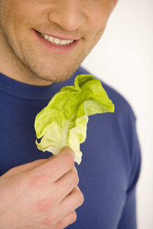 Young man holding lettuce leaf, smiling, close-up - WESTF00517