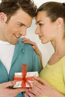 Young couple holding gift, close-up, smiling - WESTF00514