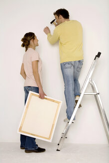 Young couple hanging up painting, man standing on ladder - WESTF00585