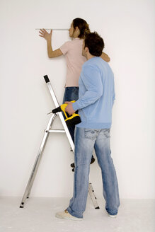 Young couple, man holding electric drill, woman measuring wall with scale - WESTF00572