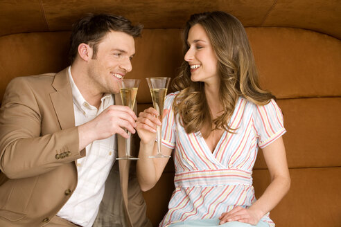 Young couple on sofa holding champagne glasses, smiling - WESTF00568