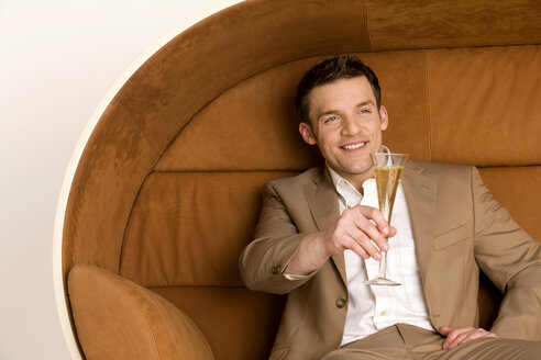 Man sitting on sofa holding out champagne glass, smiling - WESTF00565