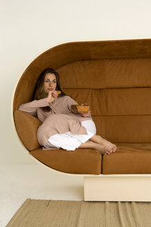 Young woman relaxing on sofa, looking away - WESTF00538