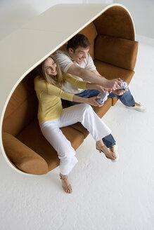 Young couple playing video game, elevated view - WESTF00526