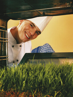 Chef looking at lawn in oven - RDF00118