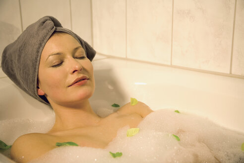 Young woman taking a bubble bath, eyes closed, close-up - MAEF00029