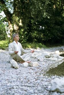 Man at river, meditating - DKF00107