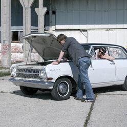 Young man examining car while woman looking - JL00111