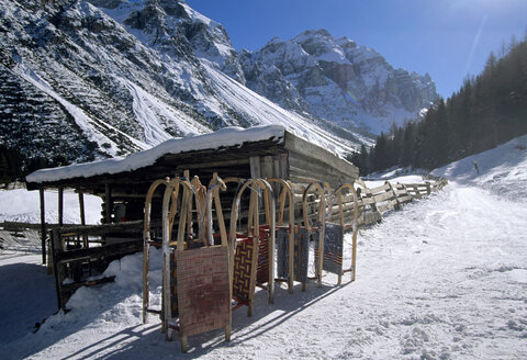 Austria, Tirol, Stubai valley, sledges in front of lodge - FFF00679