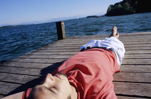 Young man relaxing on jetty, close-up - WESTF01181