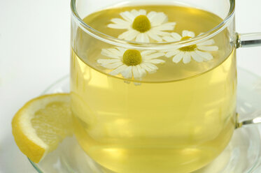 Chamomile tea in cup with flowers and lemon, close-up - WESTF01211
