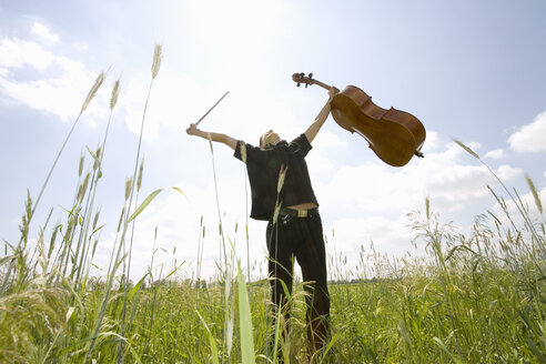 Young man standing in field with cello, low angle view - 00029MS-U