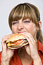 Young woman eating hamburger - WESTF01314